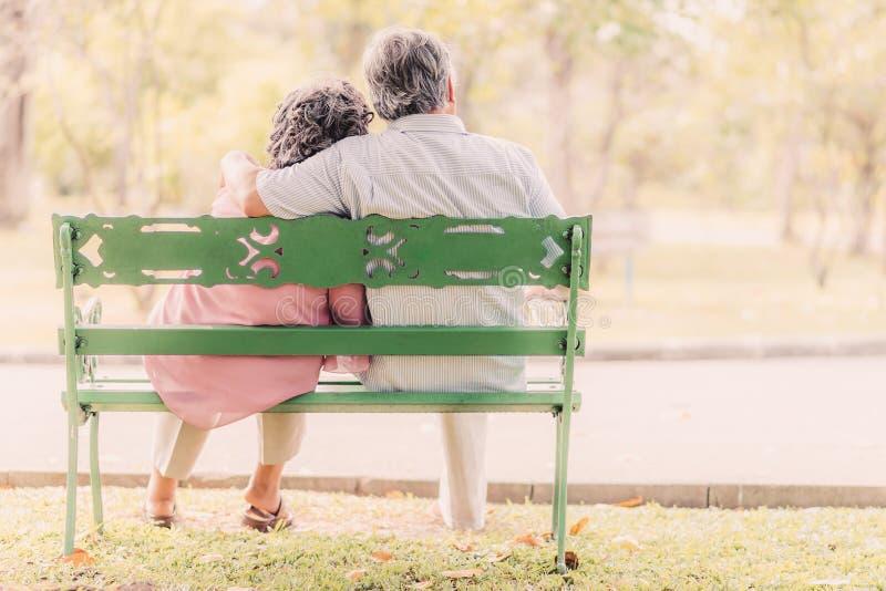 资深夫妇坐长凳在公园 库存图片