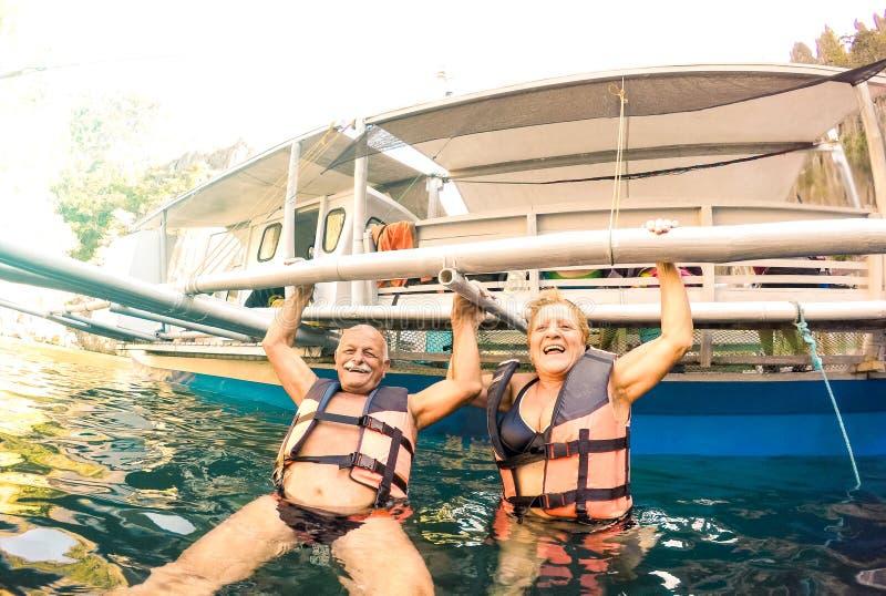 资深夫妇度假者获得真正嬉戏的乐趣在海滩在菲律宾-废气管在异乎寻常的情景的小船旅行-激活 免版税库存照片