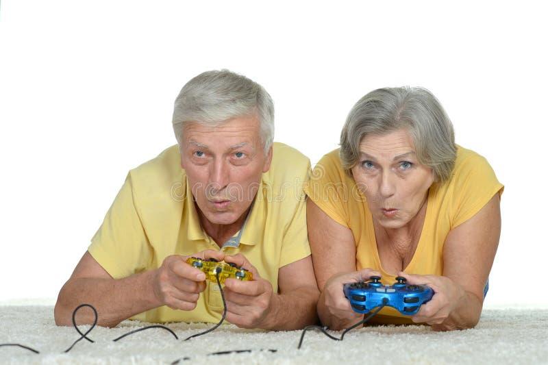 资深夫妇打电子游戏 免版税库存图片