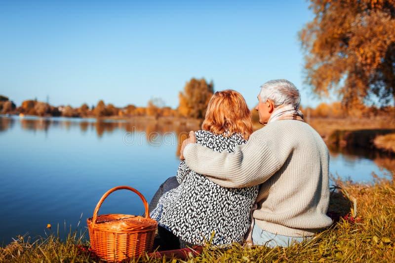 资深夫妇有野餐在秋天湖之前 愉快的享受自然和拥抱的男人和妇女 免版税库存图片