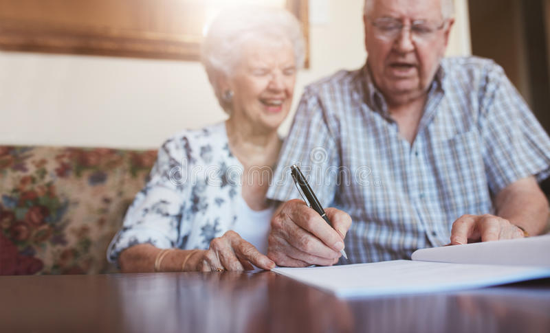 资深夫妇签署的文件在家 免版税图库摄影