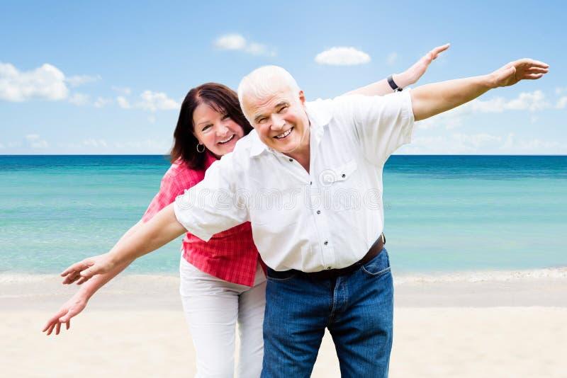 资深夫妇获得乐趣在海滩 库存照片