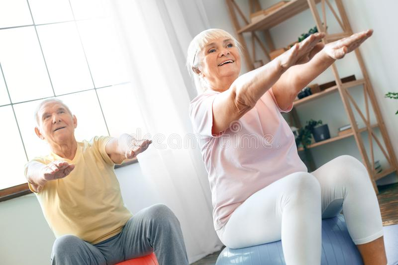 资深夫妇行使在家一起做在前面的有氧运动手 免版税库存图片