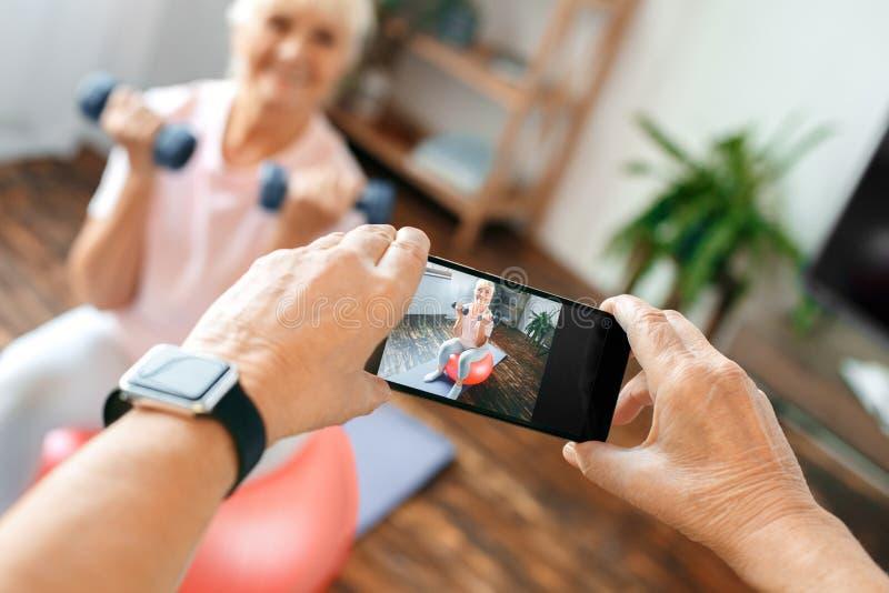 资深夫妇行使在家一起拍在锻炼球特写镜头的照片 库存图片