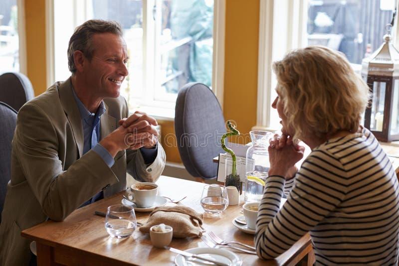 资深夫妇谈话在餐馆,侧视图 库存图片
