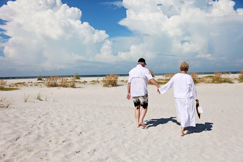 资深夫妇走的海滩 免版税库存图片