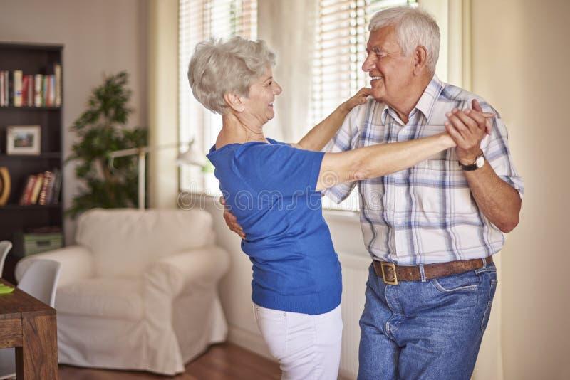 资深夫妇跳舞在客厅 免版税库存图片