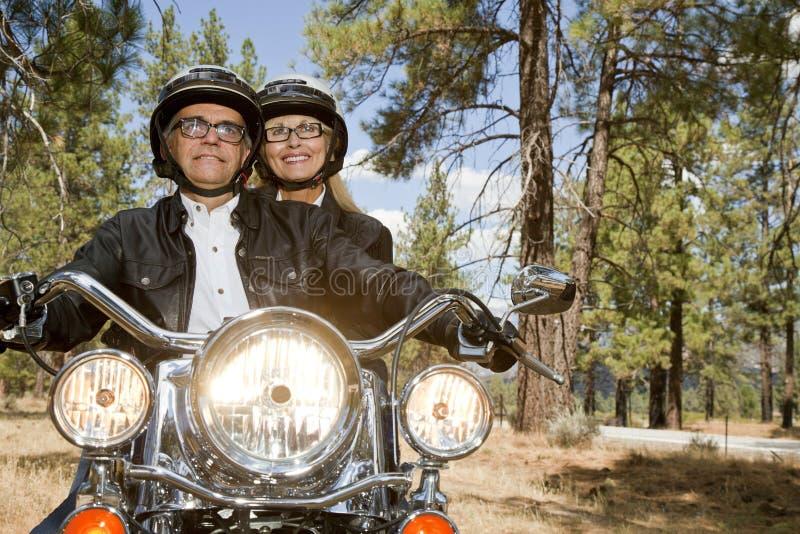 资深夫妇骑马摩托车通过森林 免版税库存图片