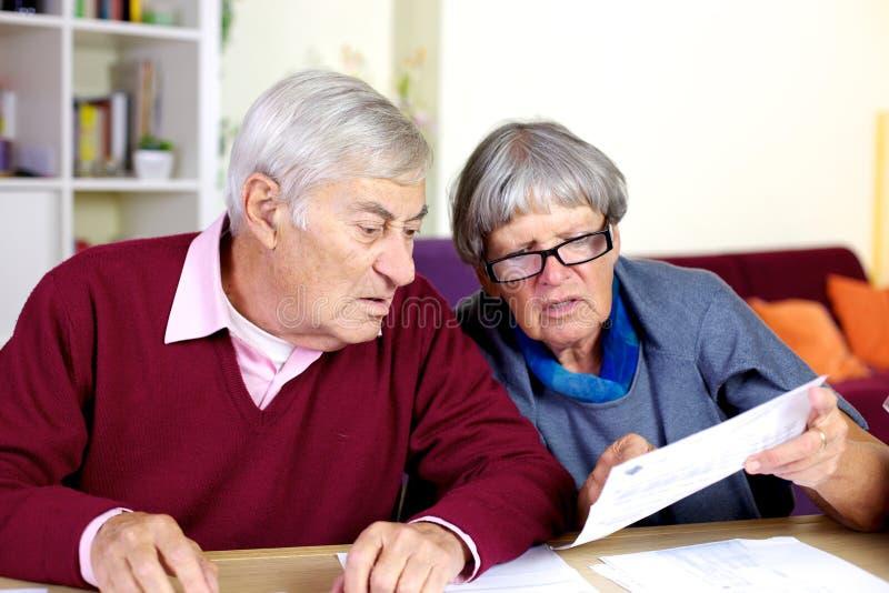 资深夫妇读书票据在家 免版税库存图片