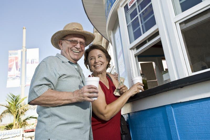资深夫妇购买饮料在食物停留演出地 免版税库存照片