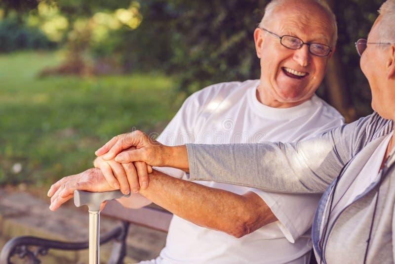 资深夫妇-在公园微笑的whil的年长夫妇的手 免版税库存图片