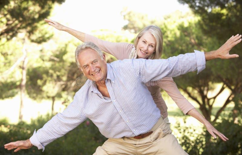 资深夫妇画象获得乐趣在乡下 免版税库存图片
