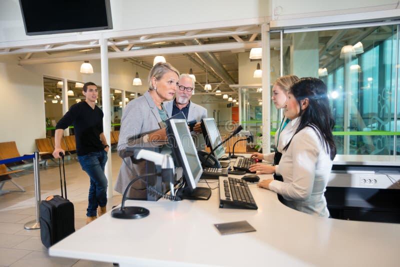 资深女实业家谈话与职员在机场 免版税库存照片