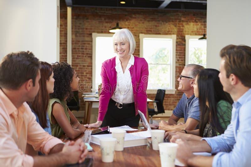 资深女性上司对办公室工作者演讲在会议上 免版税库存图片