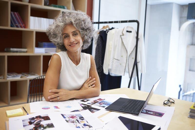 资深女性媒介创造性在看对照相机的办公室 免版税库存照片