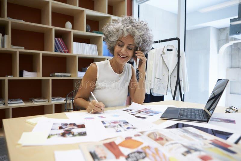 资深女性媒介创造性工作在电话 库存图片