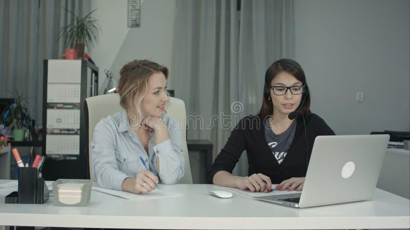 资深女性耳机的经理观看的实习生在工作和制造笔记 库存照片