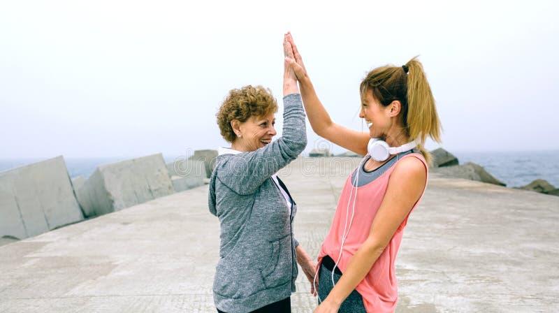 资深女运动员和女性朋友高五 免版税库存照片