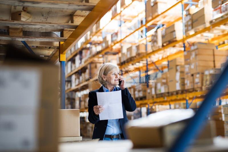 资深妇女仓库经理或监督员有打电话的智能手机的 库存图片