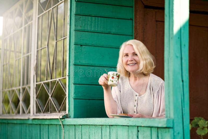 资深妇女休息和饮用的茶坐避暑别墅大阳台 免版税库存图片