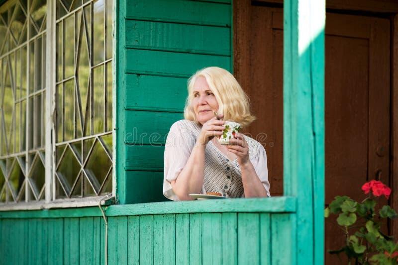 资深妇女休息和饮用的茶坐避暑别墅大阳台 免版税库存照片