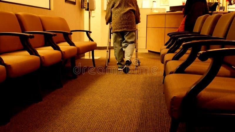 资深妇女使用一个步行者,当走向护士在诊所时 免版税库存图片
