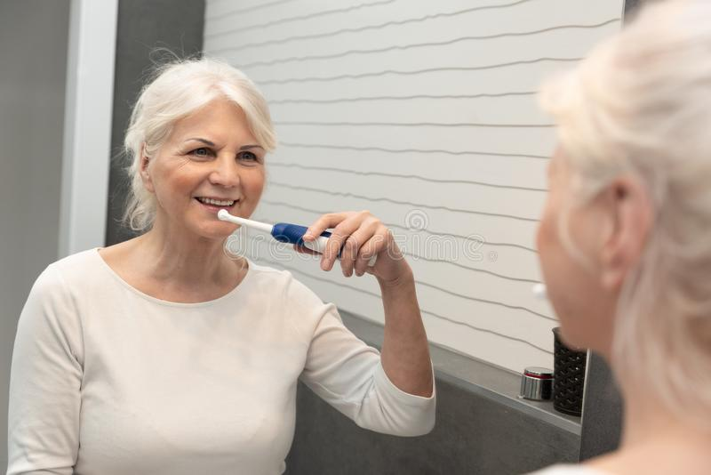 资深妇女使用的电牙刷 库存照片