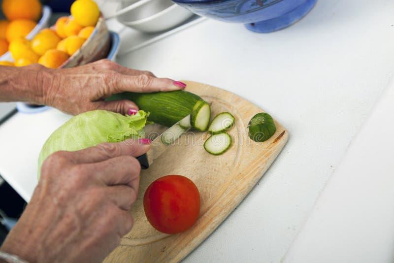 资深妇女切口菜的播种的图象在砧板的在厨房里 免版税库存图片