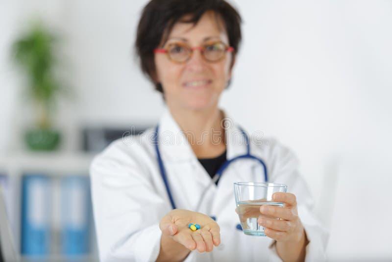 资深妇女医生提供的药片和玻璃水 库存照片