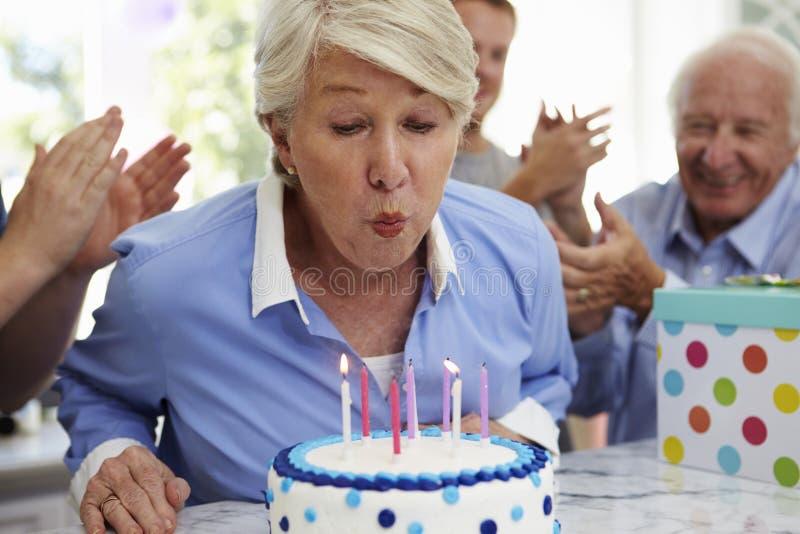资深妇女吹灭生日蛋糕蜡烛在家庭党 库存照片