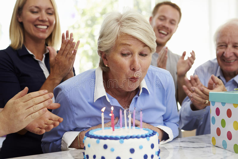 资深妇女吹灭生日蛋糕蜡烛在家庭党 免版税库存照片