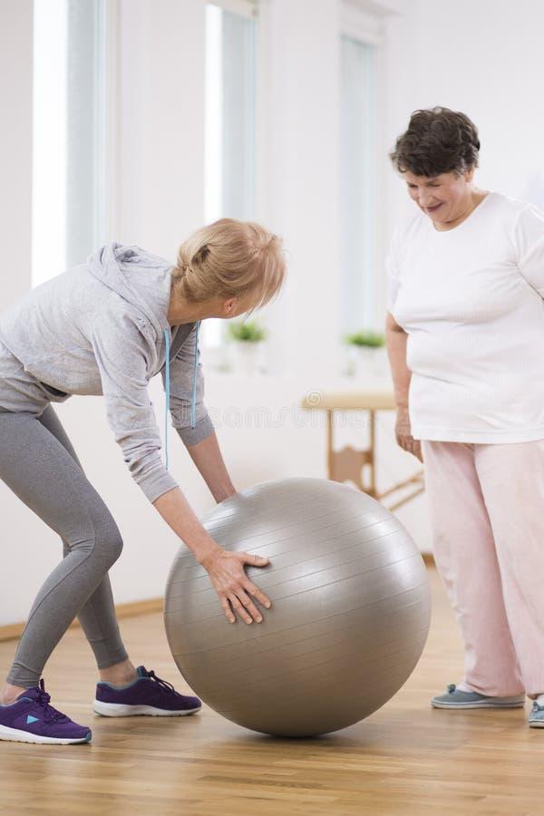 资深妇女和中年生理治疗师有体操球的 免版税库存照片