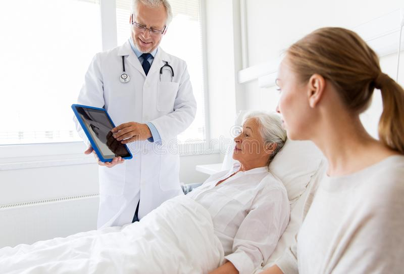 资深妇女和医生有片剂个人计算机的在医院 免版税图库摄影