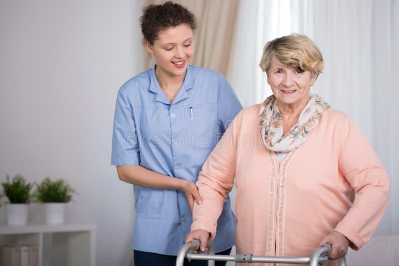资深妇女和支持的护士 免版税库存图片