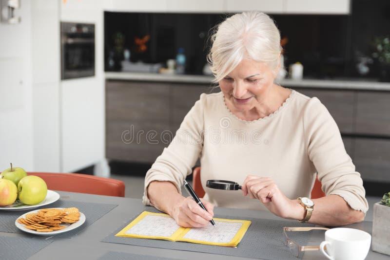 资深妇女喜欢解决纵横填字游戏 免版税库存图片