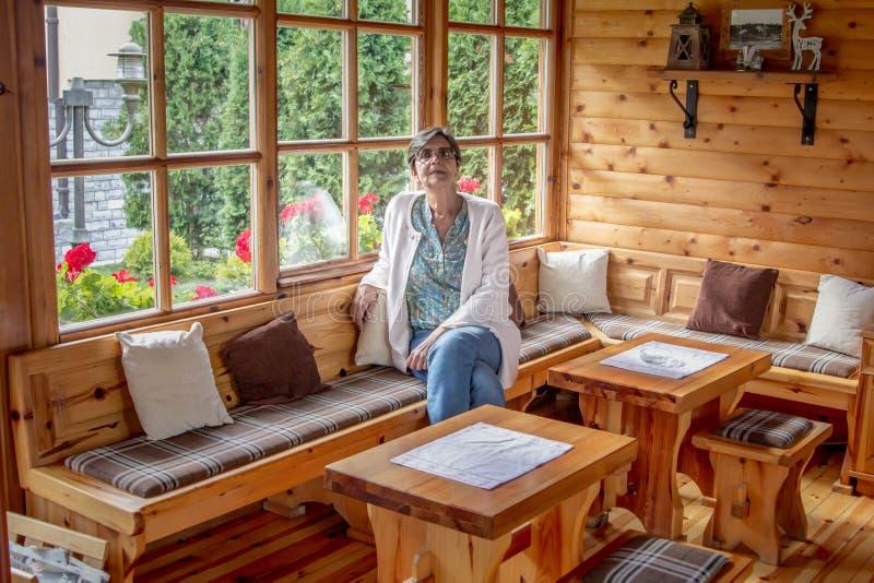 资深妇女在一个木房子里 免版税库存照片