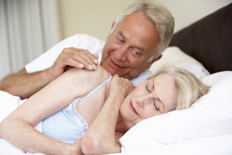 资深妇女在与好淫丈夫的床上 库存照片