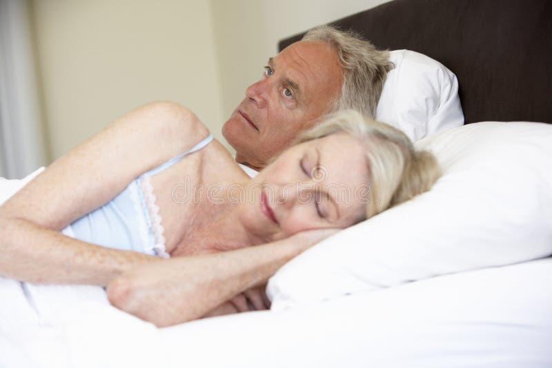 资深妇女在与担心的丈夫的床上 免版税库存照片