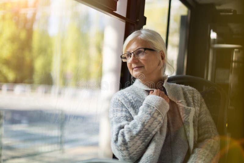 资深妇女在公共汽车上 库存照片