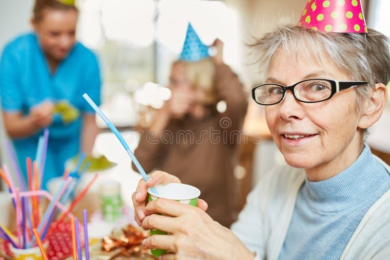 资深妇女在养老院庆祝生日 免版税库存图片