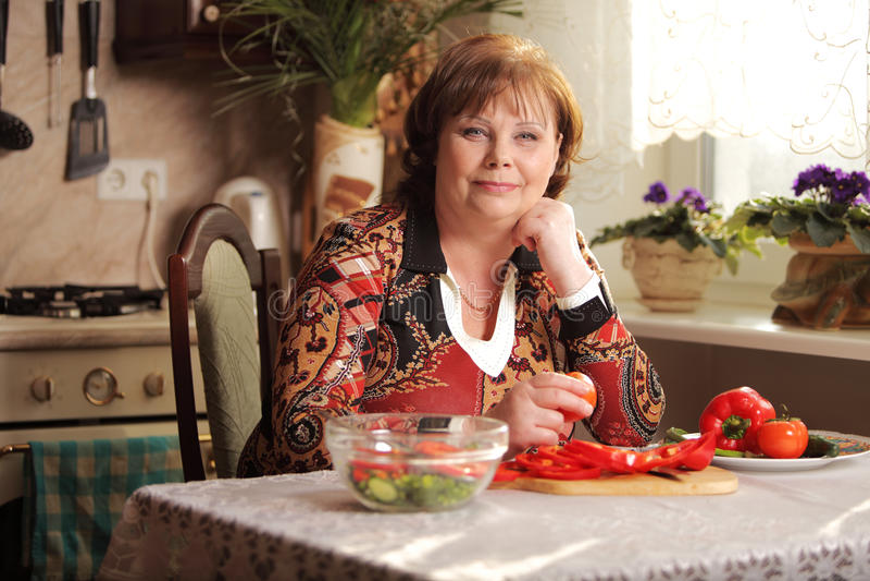 资深妇女在厨房里 免版税库存图片