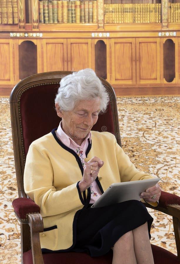 资深妇女在她的客厅读书坐片剂 免版税库存图片