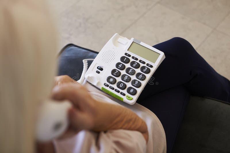 资深妇女在家使用有结束大小的钥匙的电话 库存图片