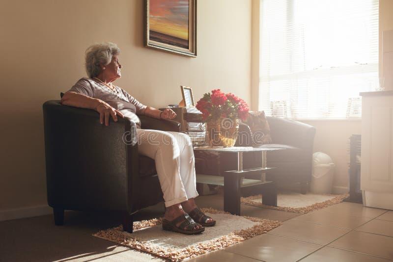 资深妇女在家单独坐椅子 免版税库存图片