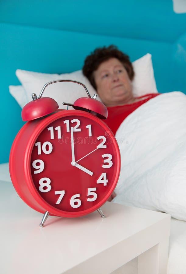 资深妇女在床上不适和遭受失眠或insomni 免版税库存图片