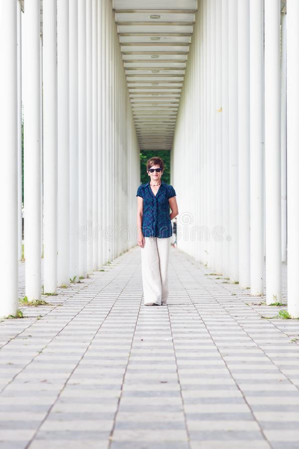 资深妇女在白色柱子走廊 免版税图库摄影