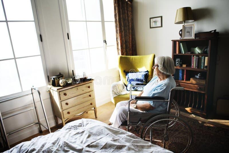 资深妇女坐单独轮椅 免版税库存图片