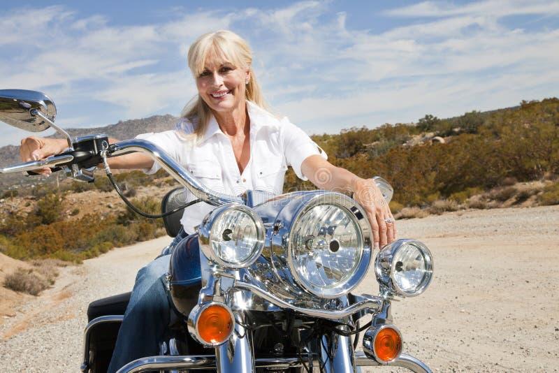 资深妇女坐在沙漠路的摩托车 库存图片