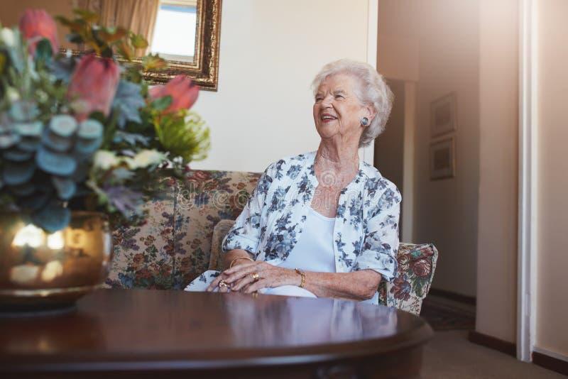 资深妇女坐沙发在晚年家 免版税图库摄影