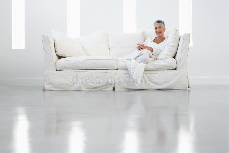 资深妇女坐沙发 库存照片